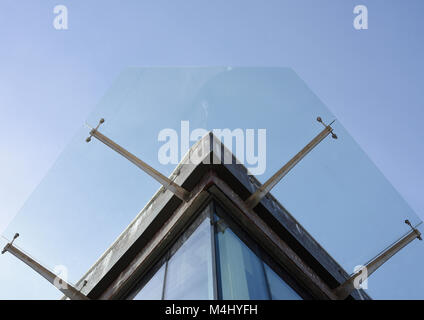 Glass canopy suspended on stainless steel brackets in v - Stock Photo