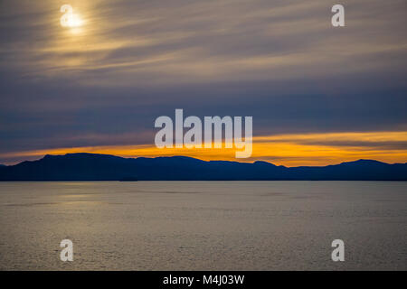 sunset and alaska mountains in mud bay - Stock Photo