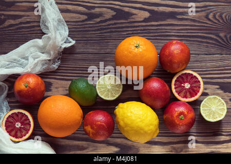 Citrus fruits over old dark wooden background. - Stock Photo