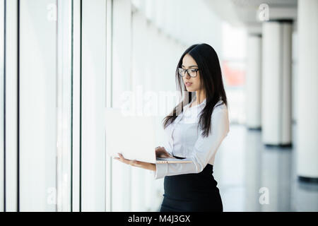 Young business woman working in her luxurious office holding a laptop standing against panoramic window with a view - Stock Photo
