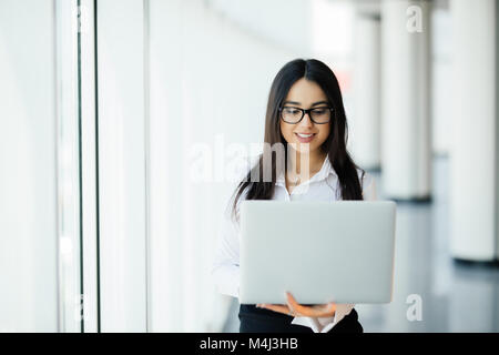 Portrait of young woman working holding laptop standing against panoramic window with city view - Stock Photo