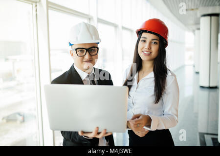 Group of engineer man and woman on construction site for check out the new project with laptop. - Stock Photo
