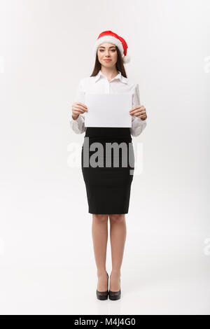 Business Concept - Beautiful young confident business woman with santa hat holding white blank paper celebrate for - Stock Photo