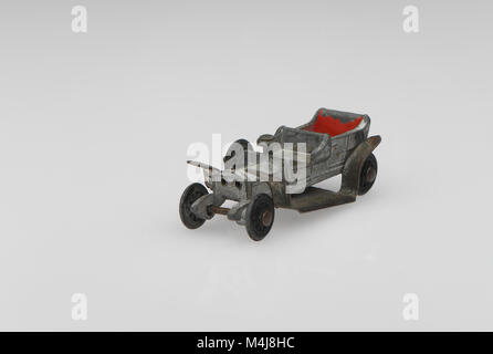 A vintage Rolls Royce Silver Ghost toy car from 1950s-60s in a well used played with condition on a white background. - Stock Photo