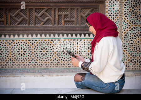 Muslim woman working on tablet in traditional clothing with red headscarf on her head beside a traditional arabesque - Stock Photo