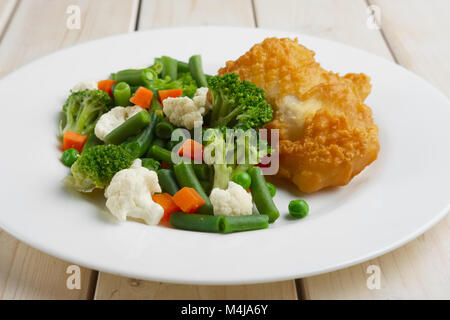 fish fillet in batter with boiled vegetables - Stock Photo