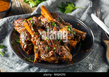 Homemade Braised Lamb Shanks with Sauce and Herbs - Stock Photo