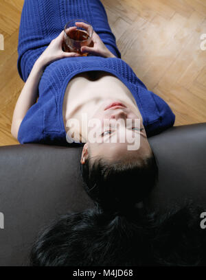 thoughtful girl on the couch with a glass of whiskey - Stock Photo