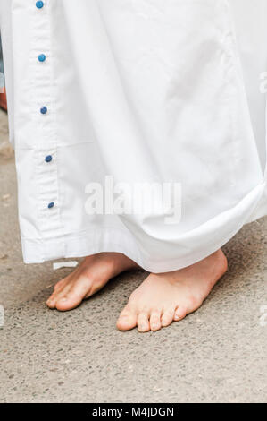 Detail of a penitent performing the penance station with bare feet. - Stock Photo