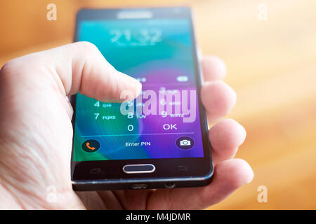 BUENOS AIRES, ARGENTINA - FEBRUARY 15, 2018: A person holding a mobile phone and entering the security code (PIN) - Stock Photo