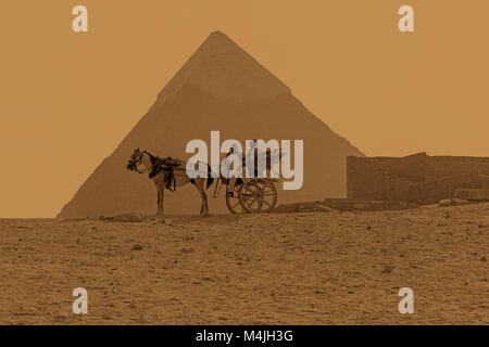 A horse and cart in front of the The Great Pyramid of Giza or the Pyramid of Khufu, Pyramids, Giza, Egypt, North - Stock Photo