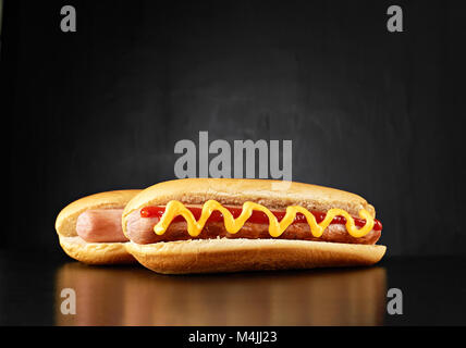Two big hotdogs with sausages, mustard and ketchup isolated on black background. Top view. - Stock Photo
