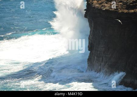 A rock cliff is being hit hard by the pounding forces of the sea, sending crashing waves up against the side of - Stock Photo