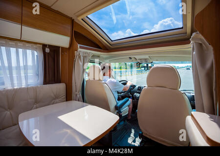 Man driving on a road in the Camper Van RV. Caravan car Vacation. Family vacation travel, holiday trip in motorhome - Stock Photo