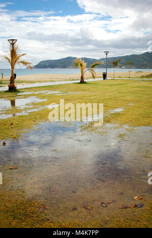 Sarti, Sithonia, Chalkidiki peninsula, Greece, Coastline, flooded lawn near beach, after storm and rain with sun - Stock Photo