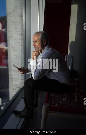 Businessman looking through window of hotel room - Stock Photo