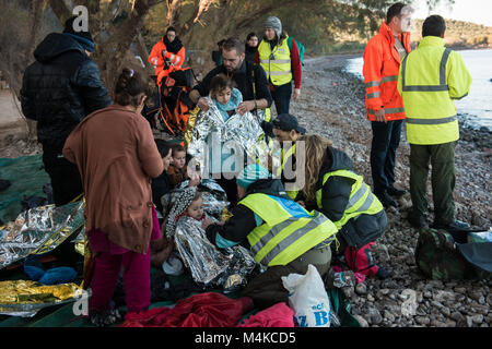 Health workers and volunteers attend a group of newly arrived refugees in a dinghy from Turkey off the coast of - Stock Photo