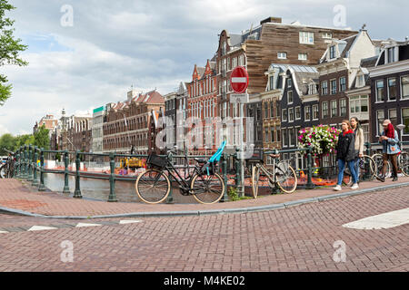 Unhappy girls walking around corner of canal in Amsterdam. One girl texting. - Stock Photo
