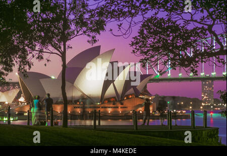 Sydney Opera House and Sydney Harbour Bridge seen at dusk across Farm Cove from Mrs Macquarie's Point. - Stock Photo