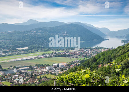 Lake Lugano, Switzerland. Picturesque aerial view of the town of Agno, lake Lugano, Lugano airport on a beautiful - Stock Photo