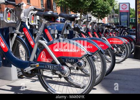 Santander bikes docking station in Bethnal Green,London,United Kingdom in summer.London bikes rental scheme.TFL - Stock Photo