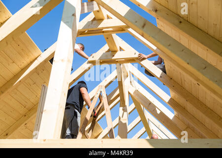 Builders at work with wooden roof construction. - Stock Photo