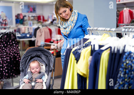 Young woman chooses clothes in a store - Stock Photo