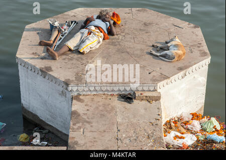 A man with one leg sleeps with a dog in the sun. Varanasi, India. - Stock Photo
