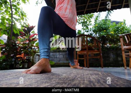 Young woman doing yoga asana Virabhadrasana Warrior Pose outside on terrace during vacation. - Stock Photo