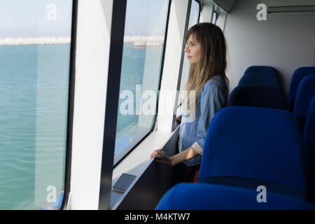 Woman looking through window while sailing in cruise ship - Stock Photo