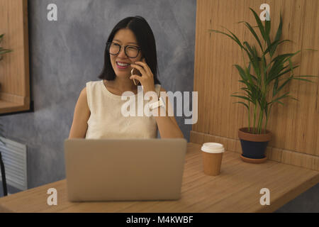 Pregnant businesswoman talking on mobile phone at desk - Stock Photo
