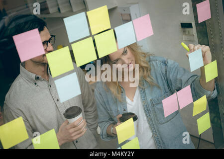 Business colleagues writing on sticky notes - Stock Photo