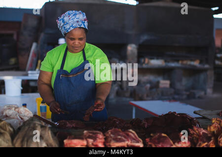 Butcher cutting meat at counter in butchery - Stock Photo