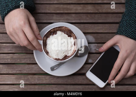 Woman having cappuccino at outdoor cafe - Stock Photo