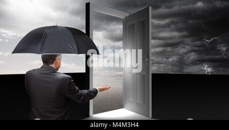Man holding umbrella and open door with surreal grey cloudy sky - Stock Photo