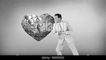 Businessman leaning against surreal heart - Stock Photo
