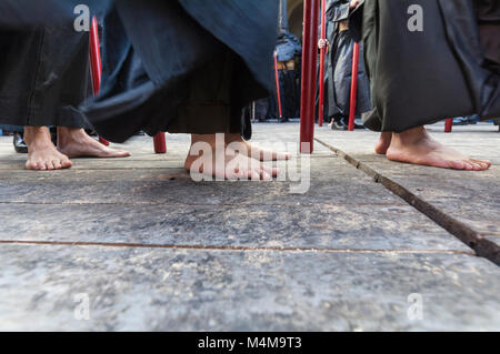 Detail of some penitents of the brotherhood of 'Santa Cruz' performing the penance station with bare feet. - Stock Photo