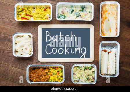 Batch Cooking Text Written On Slate With Take Away Dishes In Foil Container On Table - Stock Photo