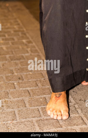 Detail of a penitent with a nail tattooed on the foot, performing the penance station with bare feet. - Stock Photo