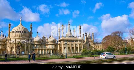 Brighton Royal Pavilion, Brighton, East Sussex, England on a clear sunny day, pedestrians walking by and a car - Stock Photo