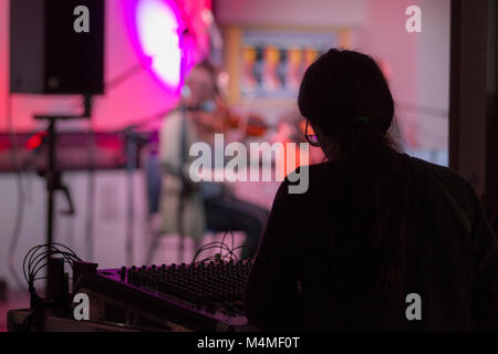recording technicians at mixing desk during concert - Stock Photo