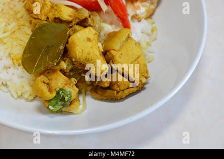 spicy salad with fried egg and chicken curry on rice - Stock Photo