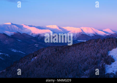 The first rays of the sun illuminate the peaks of the mountains in the winter Carpathians. - Stock Photo