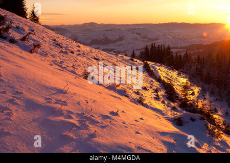 The first rays of the sun illuminate the slopes of the mountains in the winter Carpathians. - Stock Photo