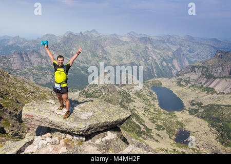 Man on the top of  hill watching wonderful scenery in mountains during  summer - Stock Photo