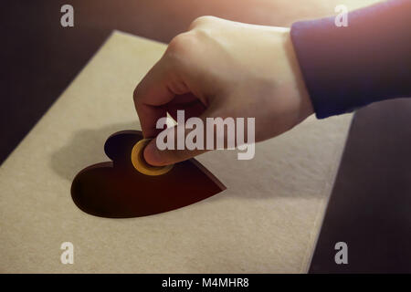 Donation Concept. Hand putting Money Coin into a Heart Shape hole on Donate Box - Stock Photo