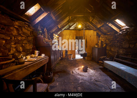 Original interior of the kitchen area with paet fire burning in The Blackhouse, 24 Arnol, Bragar, Isle of Lewis, - Stock Photo