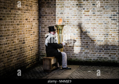 A busker plays a unique flame thrower brass tuba at Black Friars Bridge on London North Bank - Stock Photo