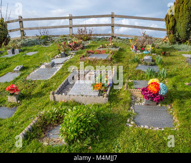 Corner of St Andrews church graveyard at Clevedon Pill on the Somerset coast with cherished and well tended graves - Stock Photo