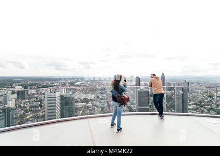 Tourist couple taking photos on a sunny Saturday afternoon from the top of Main Tower Frankfurt / Germany - May - Stock Photo